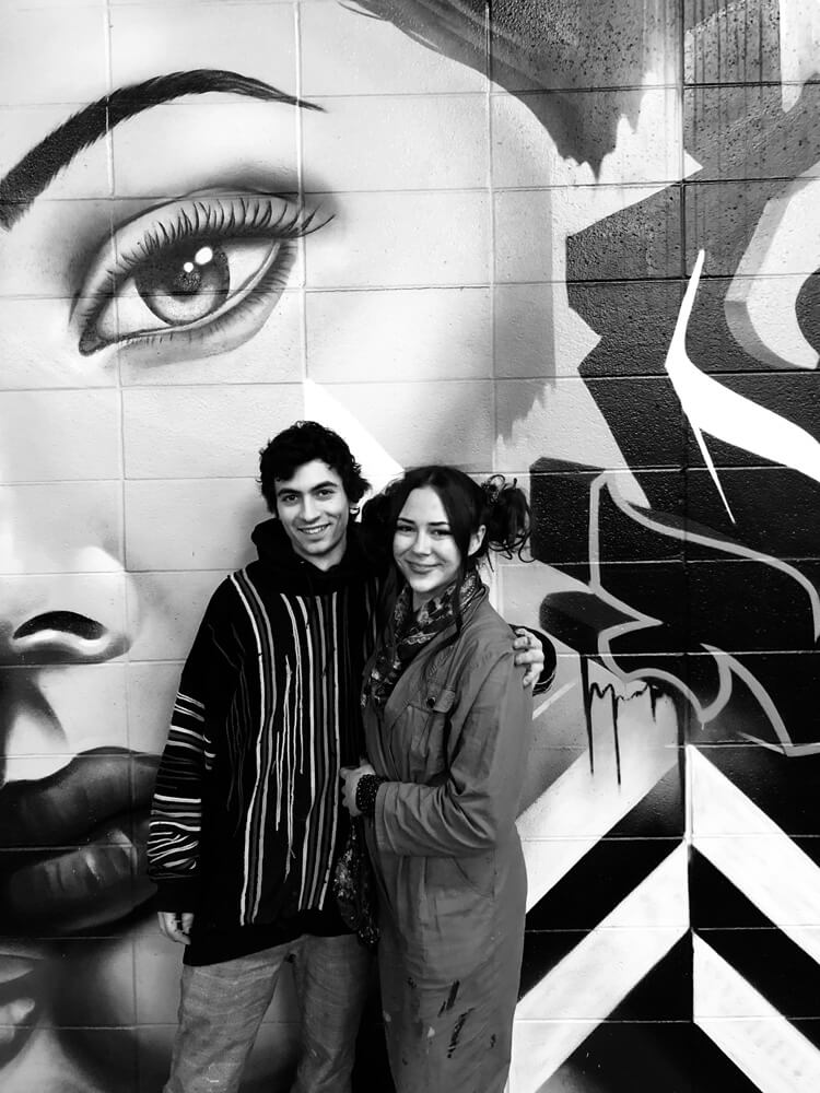 couple standing in front of graffiti art