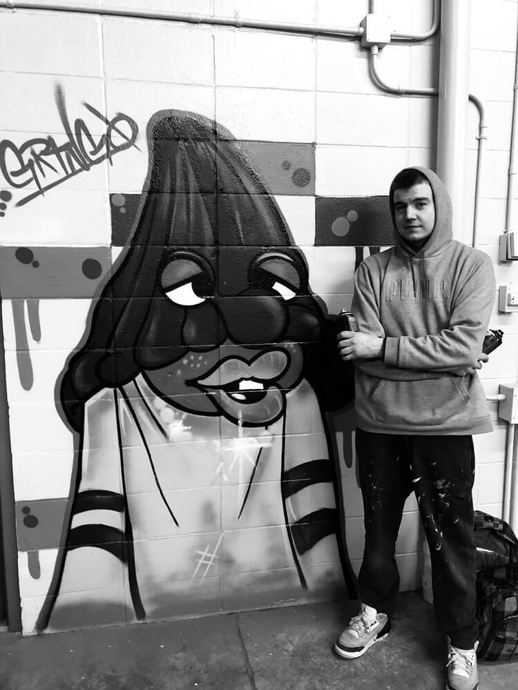 man standing in front of graffiti art at Arthur's Car Wash