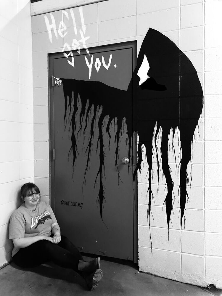 woman sitting in front of graffiti art at Arthur's Car Wash